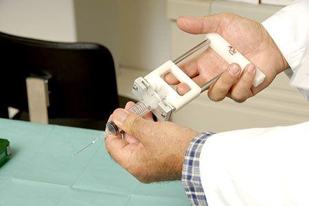 врач держит в руках шприц для биопсии