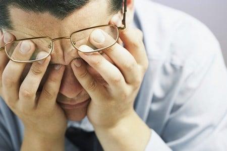 Мужчина в очках держится за глаза