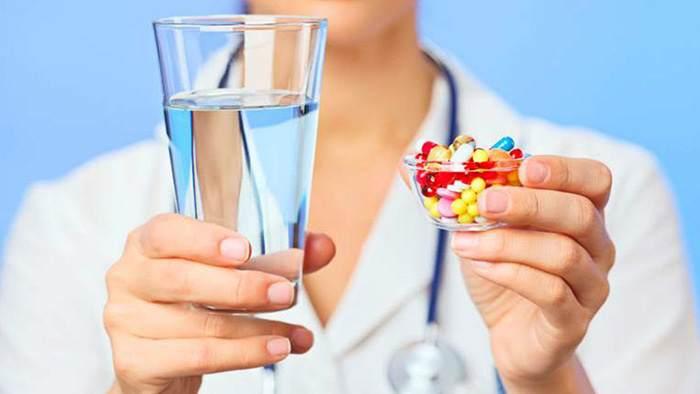 врач протягивает стакан воды и таблетки