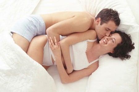 Мужчина и женщина целуются в кровати