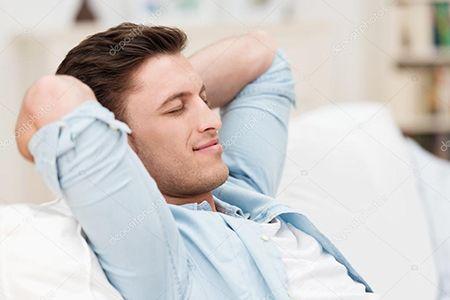 довольный мужчина сидит на диване
