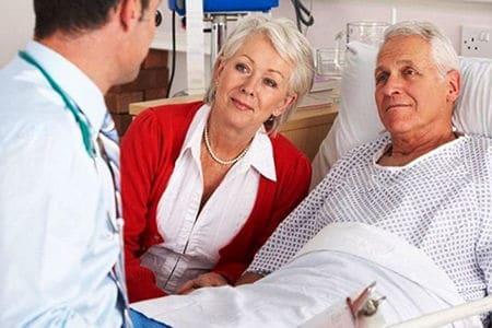 врач разговаривает с мужчиной и женщиной в палате