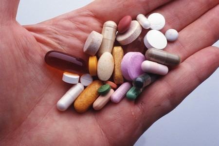 Таблетки и капсулы на руке