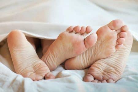 мужские и женские ноги в постели