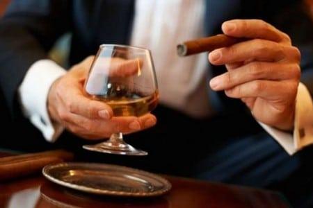 Мужчина с бокалом виски и сигарой