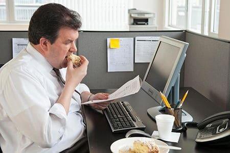 мужчина сидит в офисе за компьютером и ест