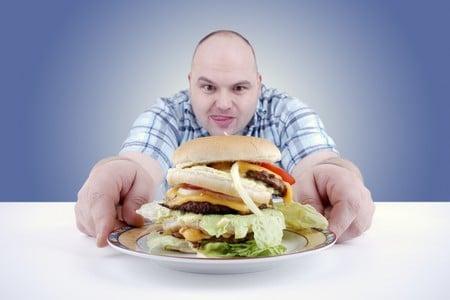 Гамбургер в тарелке перед мужчиной