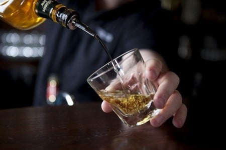 Мужчина наливает виски в стакан